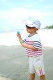 Niño en burbujas que soplan de la playa Fotografía de archivo