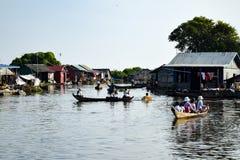 Niño en caja en el río con otros niños en barcos foto de archivo libre de regalías