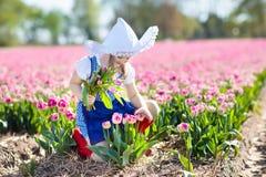 Niño en campo de flor del tulipán Molino de viento en Holanda imagen de archivo
