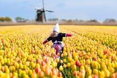Niño en campo de flor del tulipán Molino de viento en Holanda fotos de archivo libres de regalías