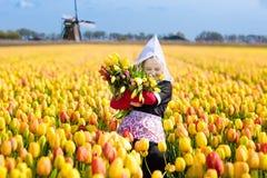 Niño en campo de flor del tulipán Molino de viento en Holanda foto de archivo