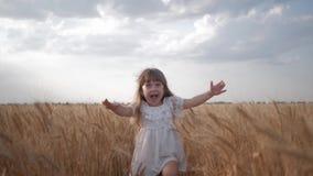 Niño en campo, niña emocional en los funcionamientos blancos del vestido con los brazos separados al encuentro a través del campo metrajes