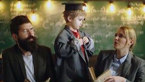 Niño en capa del traje y casquillo grandes de la graduación Educación en escuela primaria Los profesores particulares profesional metrajes
