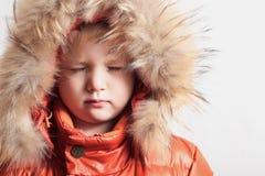 Niño en capilla de la piel y chaqueta anaranjada del invierno. ojos de la moda kid.children.closed Foto de archivo libre de regalías