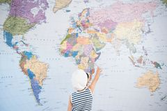 Niño en casquillo del capitán que señala en el mapa del mundo con viaje de la dirección del finger fotografía de archivo libre de regalías