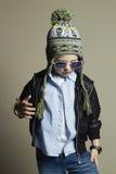 Niño en casquillo del invierno Niño pequeño de moda en gafas de sol Cabritos con estilo Imagen de archivo