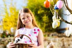 Niño en caza del huevo de Pascua con el conejito Foto de archivo