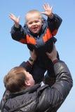 Niño en cielo en las manos del padre Foto de archivo