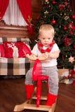 Niño en ciervos de madera en la decoración de la Navidad fotografía de archivo