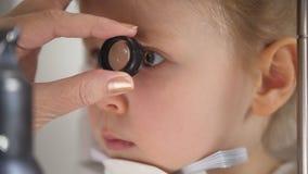 Niño en clínica de la oftalmología - muchacha rubia de la diagnosis del optometrista pequeña fotos de archivo