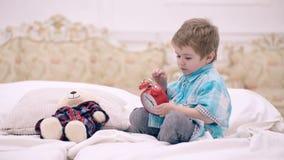 Ni?o en despertador del conjunto de dormitorio El muchacho con la cara tranquila pone el juguete preferido en la cama, hora de do almacen de video