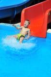 Niño en diapositiva de agua Fotos de archivo libres de regalías