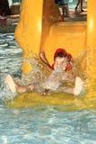 Niño en diapositiva de agua Imágenes de archivo libres de regalías