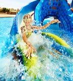 Niño en diapositiva de agua en el aquapark. Fotos de archivo