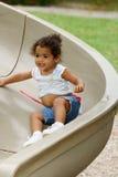 Niño en diapositiva del patio Imagen de archivo libre de regalías