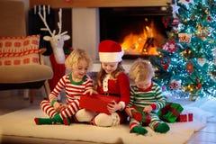 Niño en el árbol de navidad Niños en la chimenea en Navidad fotografía de archivo libre de regalías