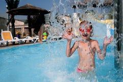 Niño en el agua azul de la piscina Fotografía de archivo