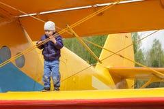 Niño en el ala de un aeroplano Imagenes de archivo