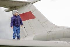 Niño en el ala de un avión de reacción Foto de archivo libre de regalías