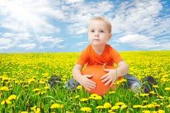 Niño en el campo de flores del diente de león, sosteniendo la calabaza Fotografía de archivo libre de regalías
