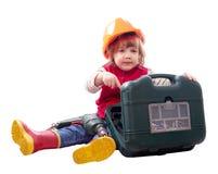 Niño en el casco de protección con el taladro y la caja de herramientas Imagen de archivo libre de regalías