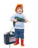 Niño en el casco de protección con el taladro y la caja de herramientas Foto de archivo libre de regalías