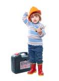 Niño en el casco de protección con las herramientas Foto de archivo libre de regalías