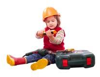 Niño en el casco de protección del constructor con las herramientas Fotos de archivo libres de regalías