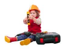 Niño en el casco de protección del constructor con las herramientas Foto de archivo libre de regalías