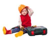 Niño en el casco de protección del constructor con las herramientas de funcionamiento Imagen de archivo libre de regalías