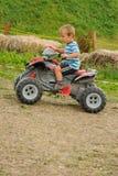 Niño en el coche de cuatro ruedas Imagen de archivo libre de regalías