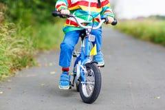 Niño en el impermeable colorido que monta su primera bici Fotografía de archivo libre de regalías