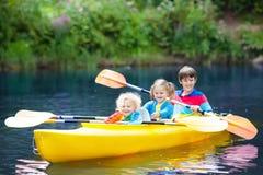 Niño en el kajak Niños en la canoa El acampar del verano Imagen de archivo