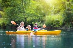 Niño en el kajak Niños en la canoa El acampar del verano Imágenes de archivo libres de regalías