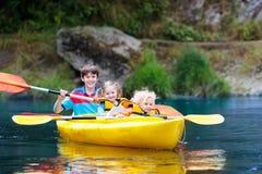 Niño en el kajak Niños en la canoa El acampar del verano Foto de archivo libre de regalías