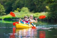 Niño en el kajak Niños en la canoa El acampar del verano Fotos de archivo