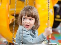 Niño en el oscilación de cadena Fotografía de archivo