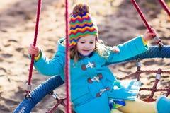 Niño en el oscilación del patio Fotografía de archivo libre de regalías