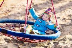 Niño en el oscilación del patio Foto de archivo libre de regalías