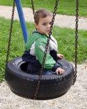 Niño en el oscilación en el patio Imagen de archivo libre de regalías