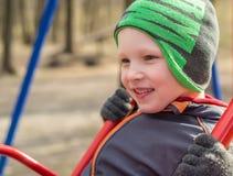 Niño en el oscilación en tiempo de primavera Fotografía de archivo