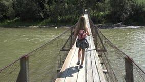 Niño en el puente en montañas, niño que camina en naturaleza, muchacha que mira un río, corriente almacen de metraje de vídeo