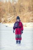 Niño en el río congelado en invierno Imágenes de archivo libres de regalías