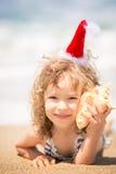 Niño en el sombrero de Papá Noel en la playa Fotografía de archivo libre de regalías