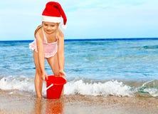 Niño en el sombrero de santa que juega en la playa. Imágenes de archivo libres de regalías