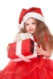 Niño en el sombrero de santa que sostiene el rectángulo de regalo rojo. Imágenes de archivo libres de regalías