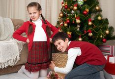 Niño en el sombrero de santa que tiene la diversión y jugar, compartiendo los regalos, decoración de la Navidad en casa, emoción  Fotos de archivo