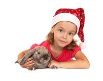 Niño en el sombrero del Año Nuevo con un conejo. Fotos de archivo libres de regalías