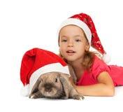 Niño en el sombrero del Año Nuevo con un conejo. Fotografía de archivo libre de regalías