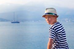 Niño en el sombrero que mira el mar y la nave Imagenes de archivo